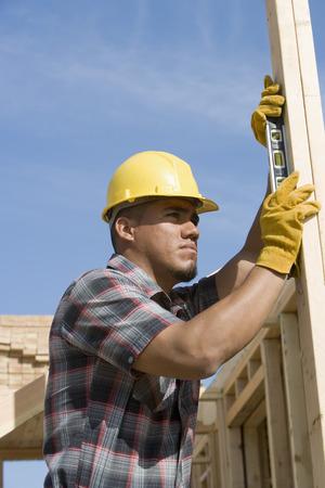 spirit level: Construction worker using spirit level on building