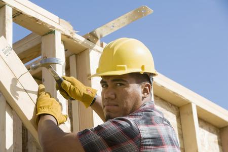 hammering: Construction worker using hammer on building