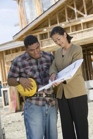 topografo: Construction worker studying blueprint with surveyor