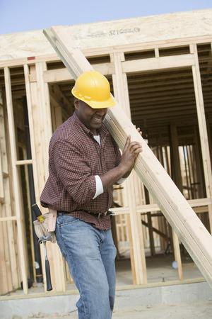 建設労働者運ぶ木の板