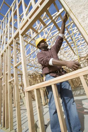 建設作業員がビルを測定 写真素材