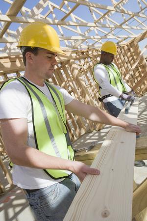 木の板を測定する 2 つの建設労働者 写真素材