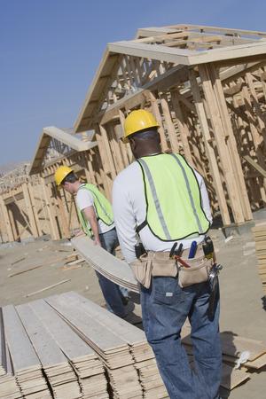 サイトで木の板を運ぶ 2 つの建設労働者