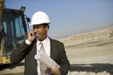 測量建設現場で携帯電話を使用して 写真素材