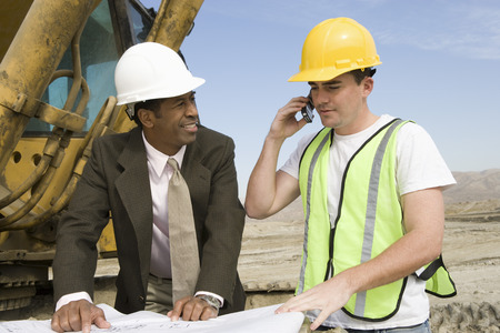 Surveyor and construction worker studying blueprint Stock Photo - 5470360