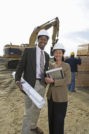 Two architects standing on construction site holding blueprints Stock Photo - 5470382