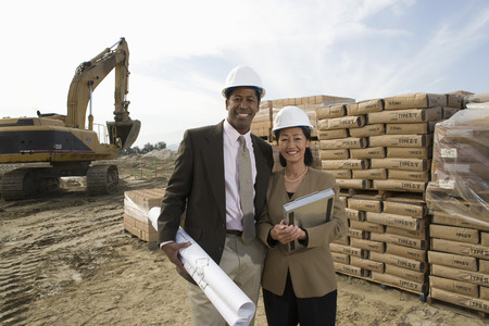 Two architects standing on construction site holding blueprints Stock Photo - 5470383