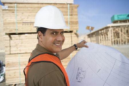 Construction worker standing on construction site and holding blueprints Stock Photo - 5470394