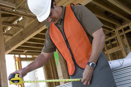 Construction worker using tape measure inside half constructed house Stock Photo - 5470400