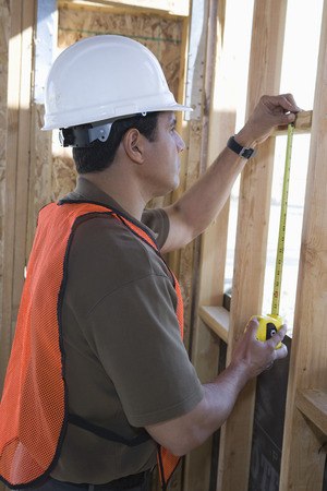 Construction worker measuring wall with measure taper inside half constructed house Stock Photo - 5470406