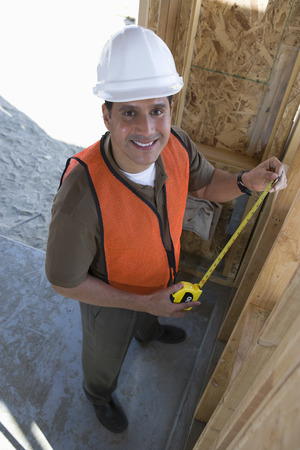 taper: Construction worker measuring wall with measure taper inside half constructed house