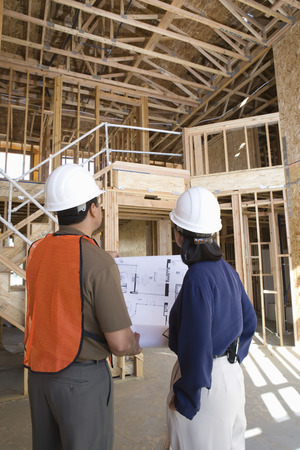 Architect and construction worker looking up while holding with blueprints inside half constructed house Stock Photo - 5470417
