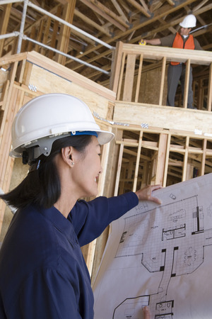 Architect and construction worker examining half constructed house Stock Photo - 5470419