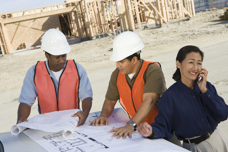 Two construction workers looking at blueprints and architect talking on phone on construction site Stock Photo - 5470424