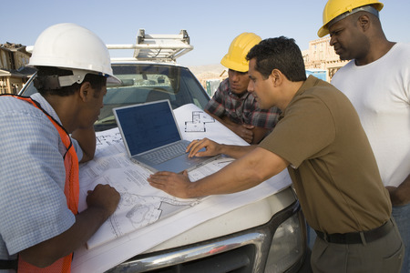 Four construction workers standing in front of car on construction site Stock Photo - 5470431