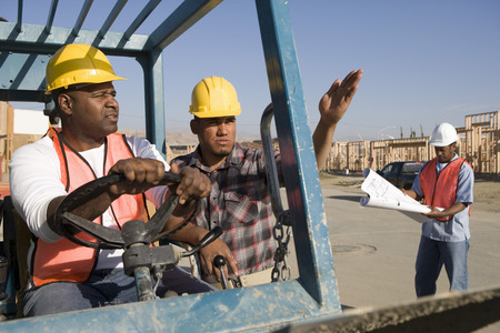 construction worker: Construction worker showing direction to another worker steering vehicle