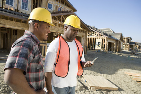 Two construction workers using mobile phone on construction site Stock Photo - 5470440
