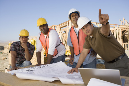 Four construction workers examining blueprints on construction site Stock Photo - 5470441