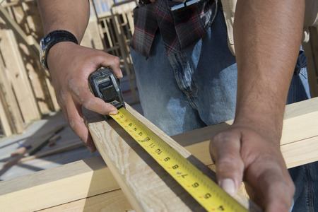 unknown age: Man measuring half constructed wall with tape measure
