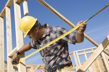 Construction worker measuring half constructed wall with tape measure Stock Photo - 5470448