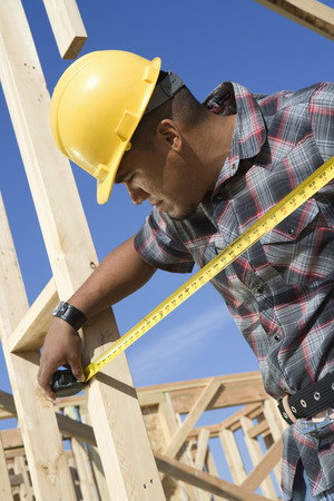 Construction worker measuring half constructed wall with tape measure Stock Photo - 5470449