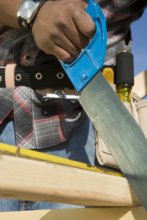 Construction worker sawing on construction site Stock Photo - 5470451