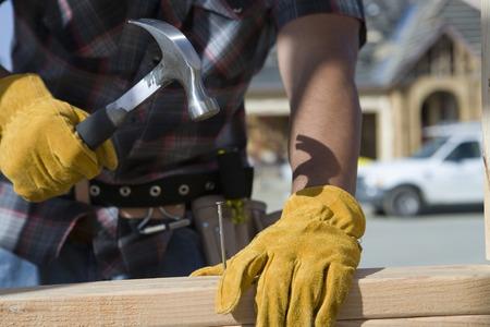 martillo: Trabajador de la construcci�n martilleo clavo a un tabl�n de madera en sitio de construcci�n  LANG_EVOIMAGES