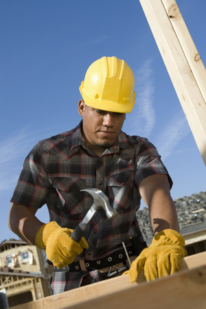 Construction worker hammering nail on construction site Stock Photo - 5470461