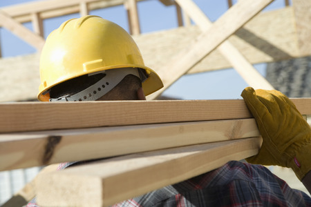 Construction worker carrying planks on construction site Stock Photo - 5470465