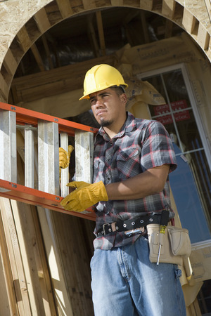 Construction worker carrying step ladder on construction site Stock Photo - 5470470