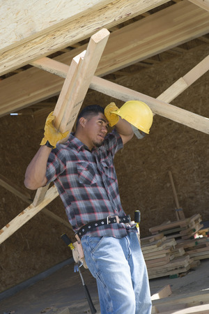 Construction worker carrying planks and wiping his forehead on construction site Stock Photo - 5470475