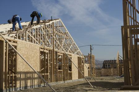 Twee bouwvakkers werken op het dak van de helft gebouwd huis