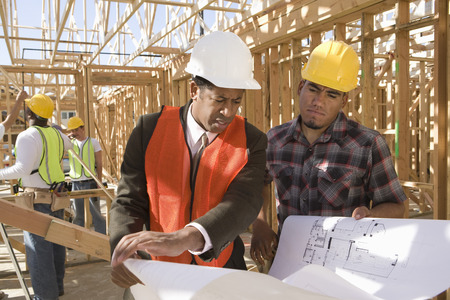 site: Architect and construction worker looking at blueprints