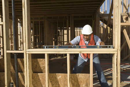 spirit level: Construction worker using spirit level on construction site