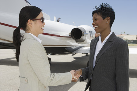 Two mid-adult businesswomen shaking hands in front of private plane on runway. Stock Photo - 5474982