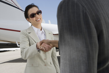 民間の飛行機の前で手を振って 2 つの半ば大人ビジネスウーマン。