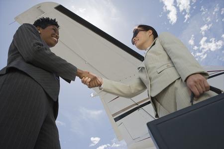 2 ミッド アダルト ビジネスウーマン ローアングル ビュー プライベート飛行機の handsin 前の揺れ。