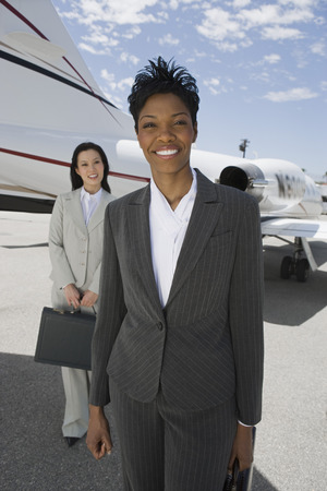 Portrait of two mid-adult businesswomen in front of private plane. Stock Photo - 5474985