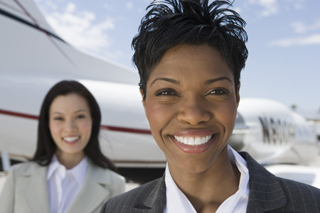 Portrait of mid-adult businesswoman standing in front of private plane. Stock Photo - 5474986