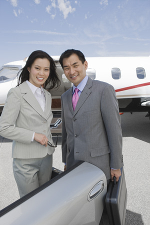Portrait of mid-adult businesswoman and mid-adult businessman standing in front of private plane. Stock Photo - 5474991