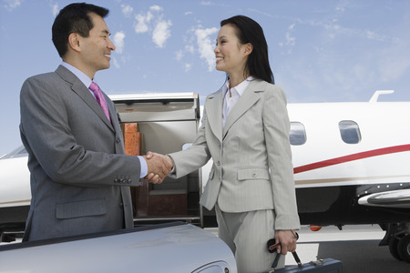 Mid-adult businesswoman and mid-adult businessman shaking hands in front of private plane. Stock Photo - 5474992
