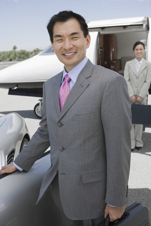 Portrait of mid-adult businessman standing in front of convertible, mid-adult businesswoman in background. Stock Photo - 5474993