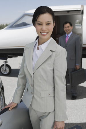 Portrait of mid-adult businesswoman standing in front of convertible, mid-adult businessman in background. Stock Photo - 5474994