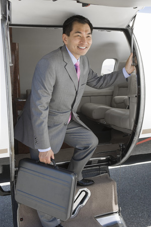 Asian businessman getting off airplane. Stock Photo - 5474995