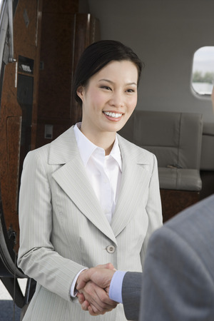 Mid-adult Asian businesswoman shaking hands with mid-adult businessman inside airplane. Stock Photo - 5474997