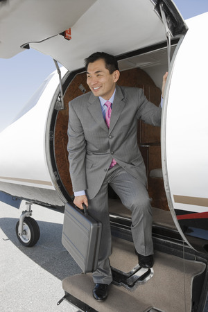 Asian businessman getting off airplane. Stock Photo - 5475000