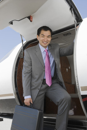 Portrait of Asian businessman getting off private airplane. Stock Photo - 5475001