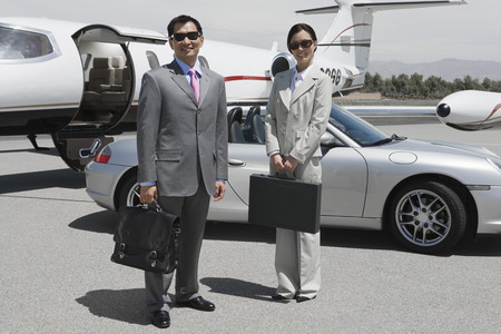 landing strip: Portrait of mid-adult businesswoman and mid-adult businessman standing in front of private plane on landing strip.