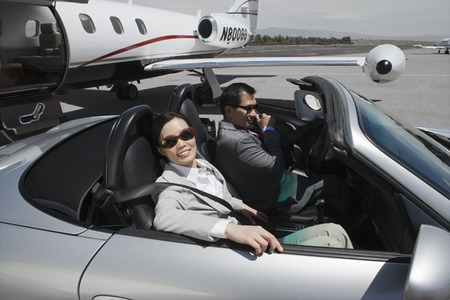 Mid-adult businesswoman and mid-adult businessman sitting in convertible on landing strip. Stock Photo - 5475006
