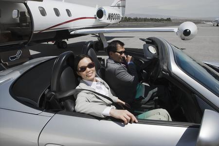 Mid-Adult empresaria y empresario mid-adult sentado en monedas convertibles en la pista de aterrizaje.  Foto de archivo - 5475006